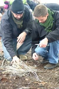 Father/Son team working together to create a twig fire for warmth.